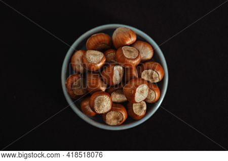 Top View Of Hazelnuts In Plate On Black Background. Healthy And High-calorie Snack