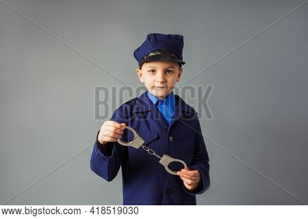 The Little Boy Stand In A Police Costume And Saluted