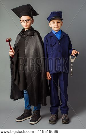 The Little Boys Dressed In A Costumes Of Officer And Judge