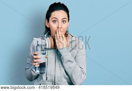 Young hispanic woman wearing sportswear holding water bottle using headphones covering mouth with hand, shocked and afraid for mistake. surprised expression