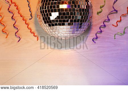Shiny Disco Ball And Serpentine Streamers On White Wooden Background, Flat Lay. Space For Text