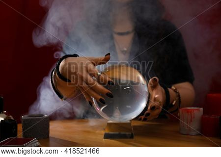 Soothsayer Using Crystal Ball To Predict Future At Table Indoors, Closeup