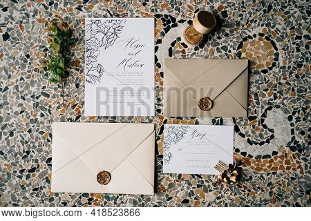 Envelopes And Invitations Sealed With Sealing Wax Lie On The Mosaic Tiles. Nearby Lies A Green Twig