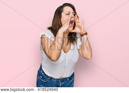 Young plus size woman wearing casual white t shirt shouting angry out loud with hands over mouth