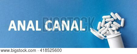 The Word Anal Canal Is Written Near Pills On A Light Blue Background. Medical, Health And Happiness