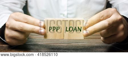 Businessman Puts Blocks With Words Ppp Loan - Paycheck Protection Program. Loan Designed To Provide
