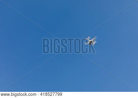 Copter With A Camera On The Background Of A Blue Sky With Clouds.