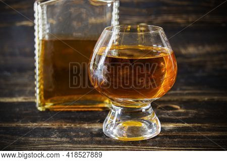 Wineglass With Cognac And Glass Flacon On Wooden Plank Surface, Close-up