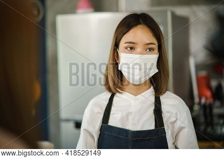 Asian Restaurant Employee Wearing Face Mask With A Bored Expression, A Woman Employee With A Frustra