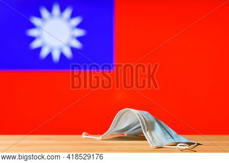 A Medical Mask Lies On The Table Against The Background Of The Flag Of Taiwan. The Concept Of A Mand
