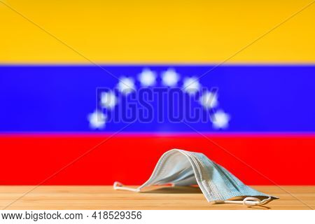 A Medical Mask Lies On The Table Against The Background Of The Flag Of Venezuela. The Concept Of A M