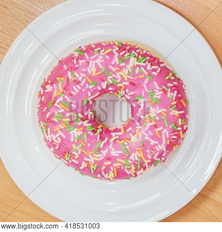 Delicious Appetizing Donut With Pink Icing On White Plate, Top View.