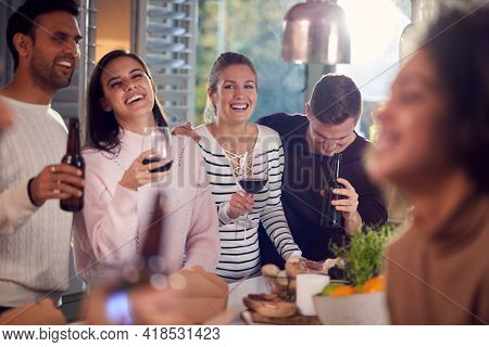 Group Of Multi Cultural Friends Enjoying Drinks Party At Home Together