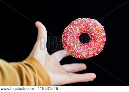 Bright Glazed Donut Close-up And Hand Grabbing It In Motion On A Dark Background