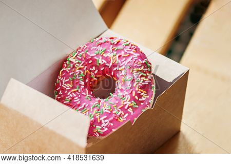 Delicious Tasty Sweet Glazed Pink Donut In Paper Box Close-up. Sale, Purchase, Delivery Of Fresh Bak