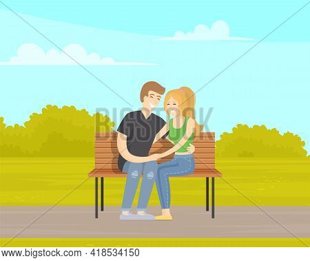 Couple On Date Outdoors Sitting On Bench. Girl And Guy Spend Time In Park In Spring. Romance Of Youn