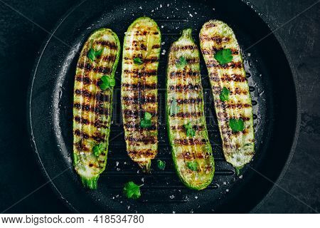 Grilled Zucchini Slices In Cast Iron Pan On Dark Stone Or Concrete Background, Top View.