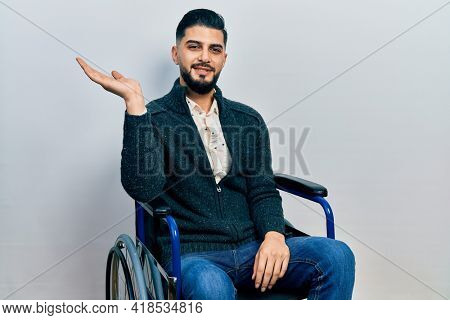 Handsome man with beard sitting on wheelchair smiling cheerful presenting and pointing with palm of hand looking at the camera.