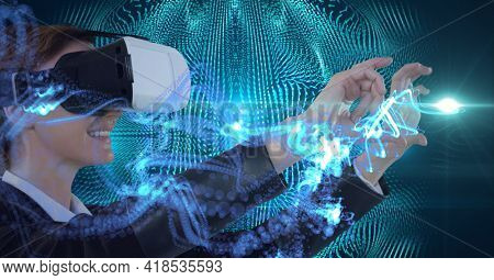 Composition of green light trails over woman wearing vr headset and touching virtual screen. global connection, virtual reality and technology concept digitally generated image.