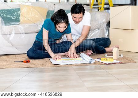 Asian Couple, Husband And Attractive Wife Looking At Blueprint And Discuss About Renovating The Old