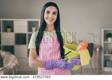 Portrait Of Attractive Cheerful Long-haired Girl Holding In Hands Bucket With Cleanup Supplies At Li