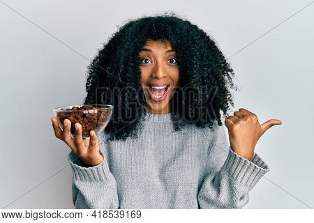 African american woman with afro hair holding raisins in bowl pointing thumb up to the side smiling happy with open mouth