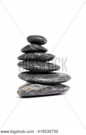 Zen Stones Or Black Pebbles Stacked On Top Of Each Other Like A Pyramid, Isolated On White Backgroun
