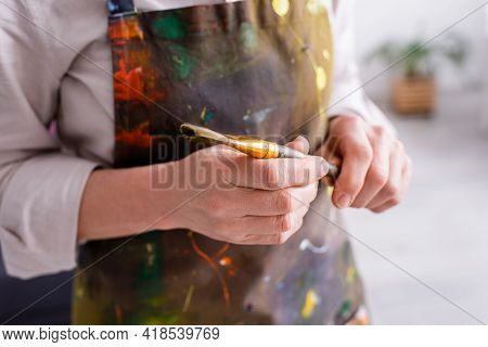 Partial View Of Middle Aged Artist In Apron With Spills Holding Paintbrush.