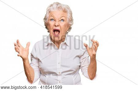 Senior grey-haired woman wearing casual clothes crazy and mad shouting and yelling with aggressive expression and arms raised. frustration concept.