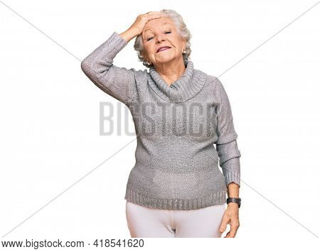 Senior grey-haired woman wearing casual winter sweater smiling confident touching hair with hand up gesture, posing attractive and fashionable
