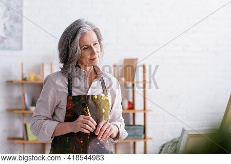 Middle Aged Artist In Apron With Spills Holding Paintbrush At Home.