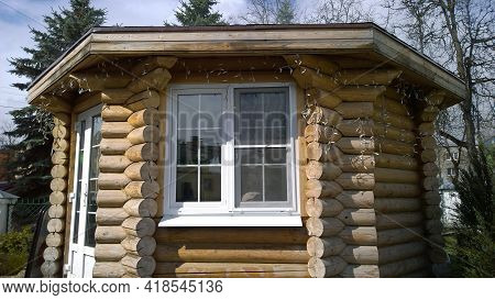 Old Wooden House Made Of Beams With Modern Plastic Window In Disrepair From Fairy Tale. Logs Constru