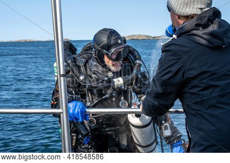 April 17, 2021 - Hamburgsund, Sweden: A Scuba Diver Have Just Return To The Dive Boat And Gets Help