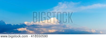 A Cumulus Curly Cloud Illuminated By The Evening Sun In The Blue Sky. Panorama
