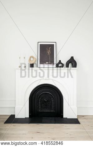 Vertical View Of White Modern Fireplace With Picture Frame, Vase And Candle In Candlestick At Contem