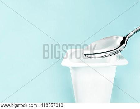 Yogurt Cup And Silver Spoon On Mint Background, White Plastic Container With Yoghurt Cream, Fresh Da