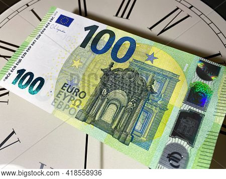 One New Hundred Euros Of 2013 Is On The Watch, Clock, The Dial With Roman Numerals. Time Is Money