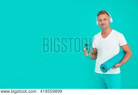 Water Intake Helps With Thirst. Athlete Hold Water Bottle And Yoga Mat Blue Background. Thirst And D