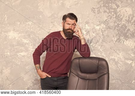 Trendy Outfit Perfect For His Style. Brutal Hipster Stand At Office Chair. Bearded Man In Casual Sty