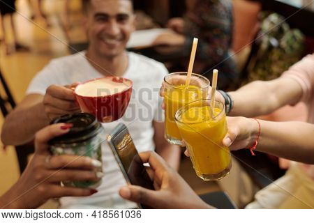 Five Hands With Glasses Of Juice, Coffee And Smartphones, Clink Glasses, On The Background Of A Wood