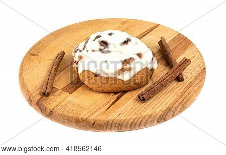 Sugar Glazed Sweet Cinnabon Bun On A Cutting Board Over White Background. Cinnamon Sticks. Homemade
