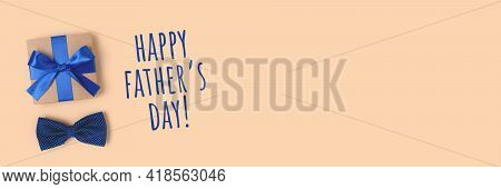 Happy Fathers Day. Banner With Gift Box And Bow Tie. Present Tied With A Blue Ribbon On A Beige Back