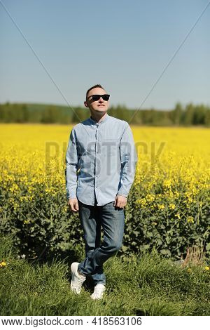 A Young Man In Sunglasses Is Walking And Having Fun Through A Sunny Yellow Rapeseed Field, The Conce