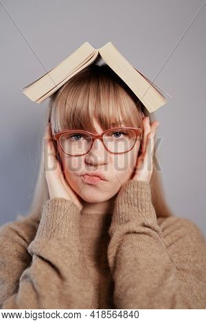Caucasian Female University Student Wearing Eyeglasses And Beige Sweater With Book On Head Showing H