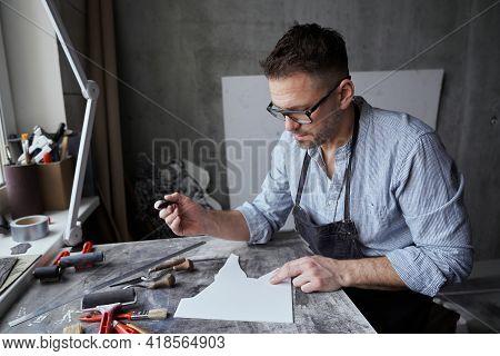 Bearded Male In Apron And Eyeglasses Making Sketch On Linoleum. Linocut Artist Printmaking Manufactu