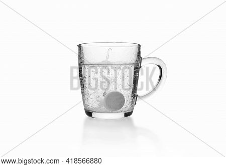 Soluble Fizzy Tablet On The Bottom Of Transparent Glass Mug On White Background