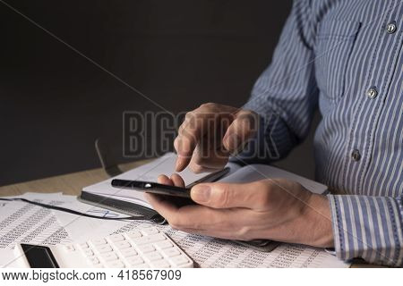 Businessman With Mobile Phone In Hands And Financial Documents With Numbers.