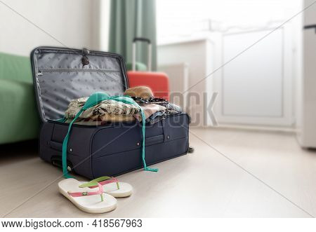 Open Suitcase Full Of Summer Vacation Or Holiday Things In The Living Room