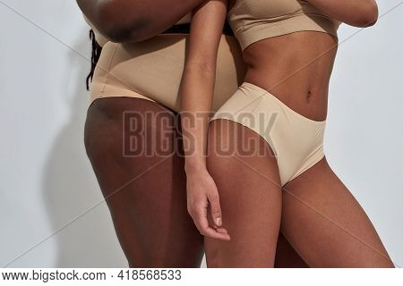 Close Up Of Bodies Of Two African American Women In Beige Underwear With Different Body Sizes Standi
