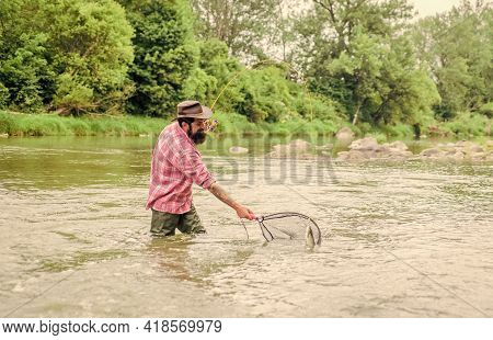 Fishing Hobby. Bearded Brutal Fisher Catching Trout Fish With Net. If Fish Regularly You Know How Re